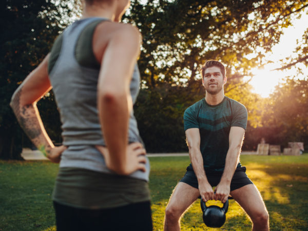 Young man doing weight training with personal female trainer in the park. Caucasian male exercising with kettlebell.