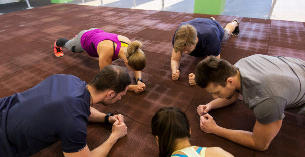 fitness, sport, exercising, training and healthy lifestyle concept - group of people doing plank exercise in gym