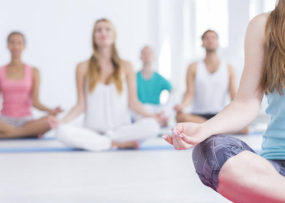 Cropped shot of people doing yoga in a studio