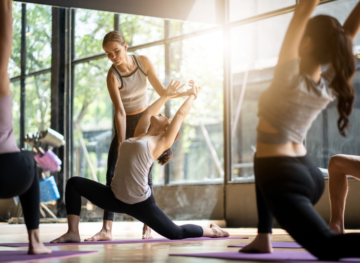 Group of multi ethnics people learning Yoga class in fitness club. Female Caucasian instructor coaching and adjust correct pose to Asian girl student at front while others doing follow them.